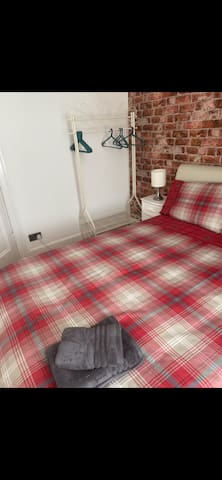 Double bed, clothes rail with hangers, two bedside cabinets with lamps and a chest of drawers.