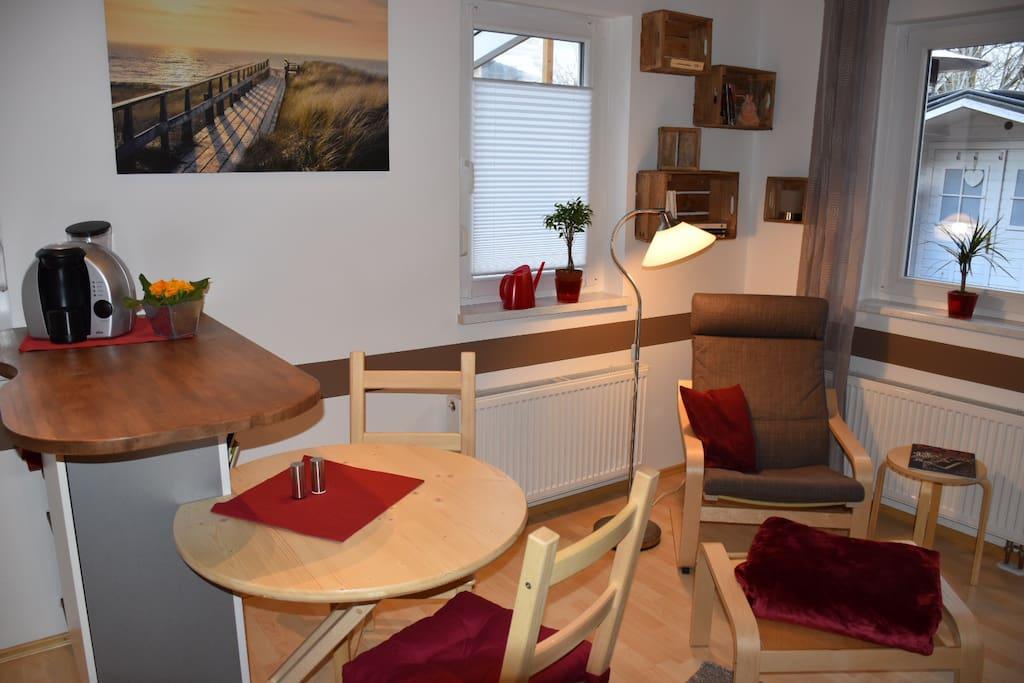 Küchentheke mit Essplatz und Sitzgelegenheit sowie Wohnbereich mit Sessel.