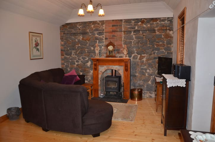 Lounge room with feature bluestone wall and wood heater