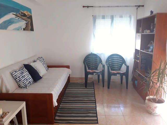 Sala com sofá-cama, varanda e duas janelas laterais