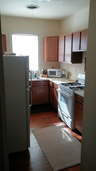 Bright, sunny kitchen with gas burners, oven,  refrigerator, toaster oven, microwave, coffee machine, and dish washer.