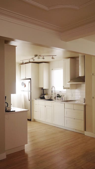 Kitchen with white cabinets, quartz countertop dishwasher, microwave, oven, coffee machine, stovetop, ninja blender, toaster.