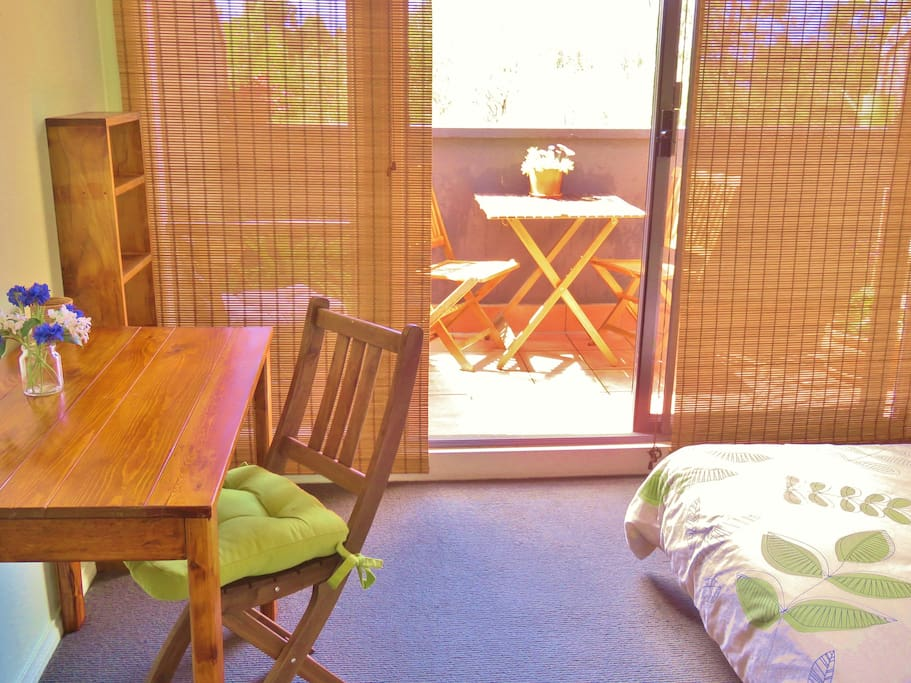 The room has a desk, chair, lamp, book case, built in robes, heater and fan