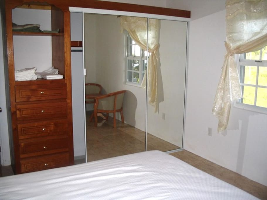 Queen sized bed with screened in windows, net around bed and airconditioner.