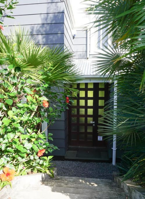 Welcome to Garden House -  walk down through palms and hibiscus flowers to the front door.