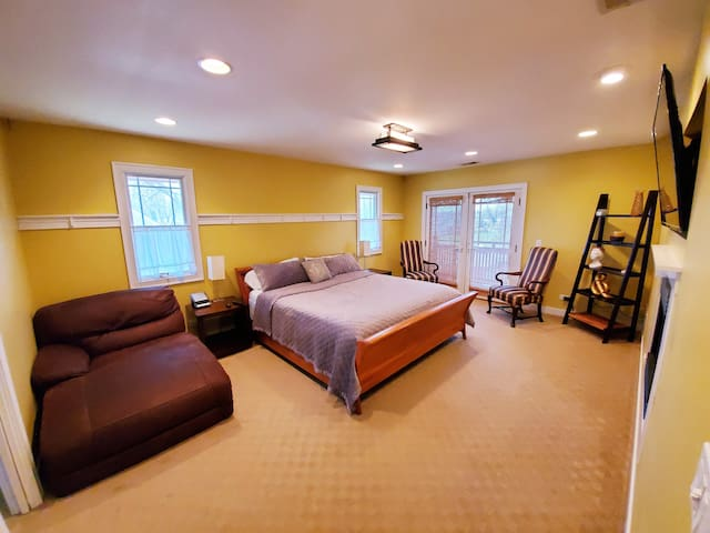 Master - King Bed (located on 2nd floor) with 2 chairs for seating, chaise, tv over fireplace.  Balcony with views to the backyard.