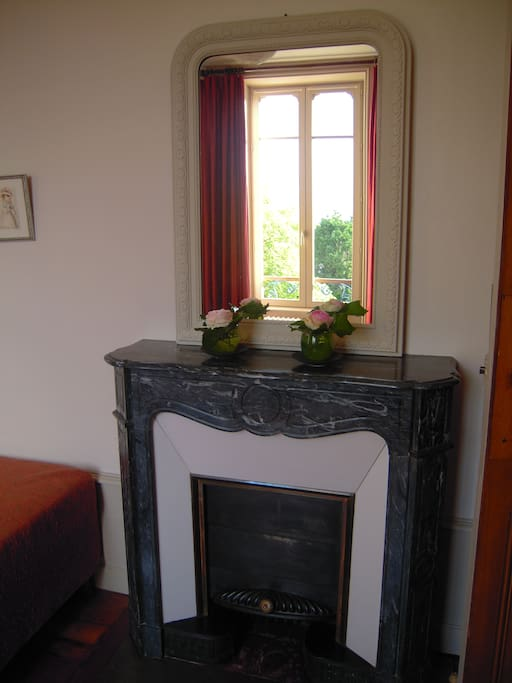 1900 fire place with a mirror belonging to the house reflecting the window and its red linen curtains/ Cheminée 1900 et son mirroir qui reflète la fenêtre aux rideaux de lin rouges