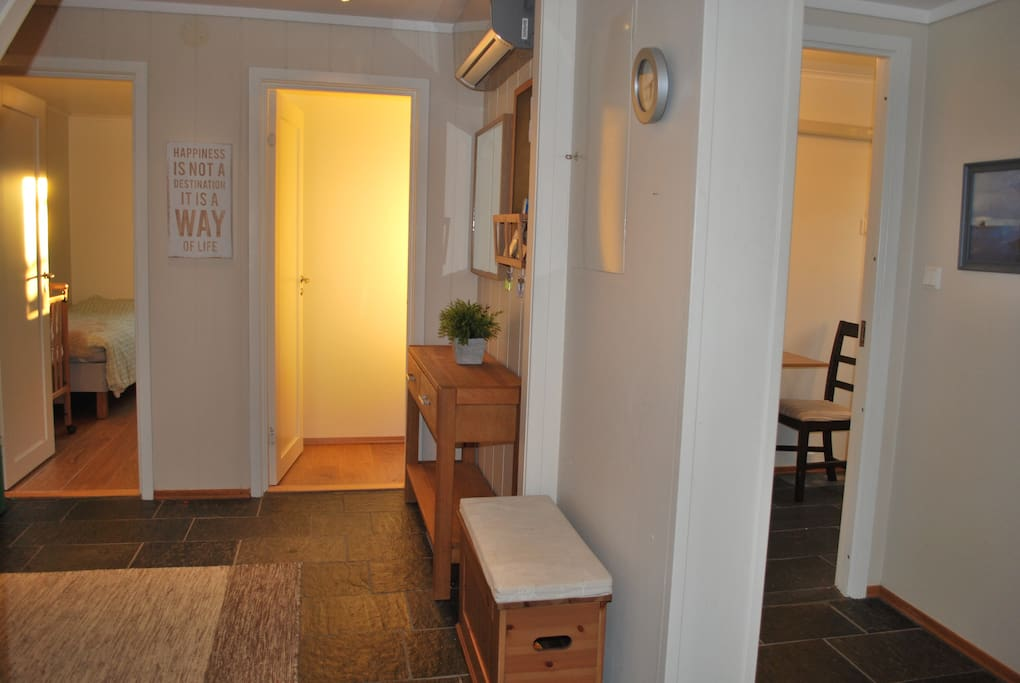 Hallway showing the two bedrooms (to the left) and kitchen and bath (to the right). Beautiful heated stone tile floor. Heat pump with air condition function. Closet available next to the bath.