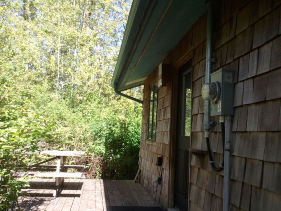 The main entrance to the cottage has a deck with wooden picnic table nested in a private bower of native bushes
