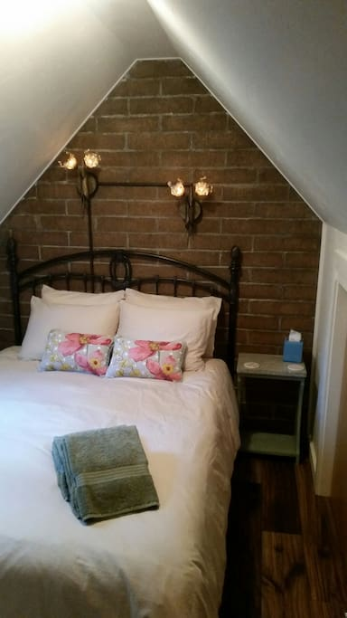 Queen size bed in upstairs bedroom. Also in this room is a sky light and a cozy fireplace heater.