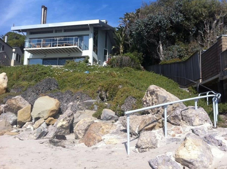 View of the house from the beach, showing the handrails leading to the sand