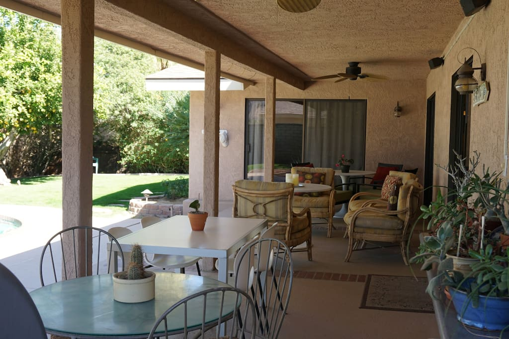 Covered porch overlooking pool and gated back yard