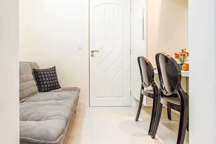 Porta de entrada para o Stúdio. Essa pequena sala, possui um sofá cama, uma mesinha, telefone (Para ligações locais). Internet, Tv à cabo, ar condicionado, televisão, e um armário.