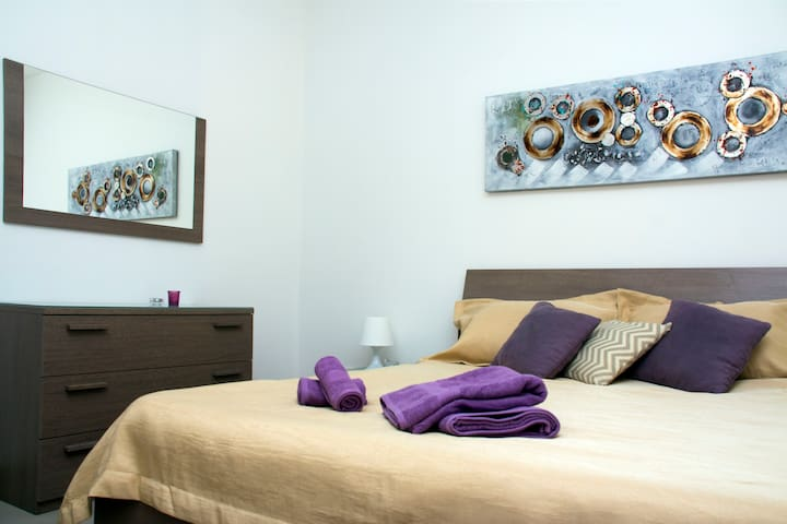 The main bedroom with a neatly made bed and two small bedside tables.