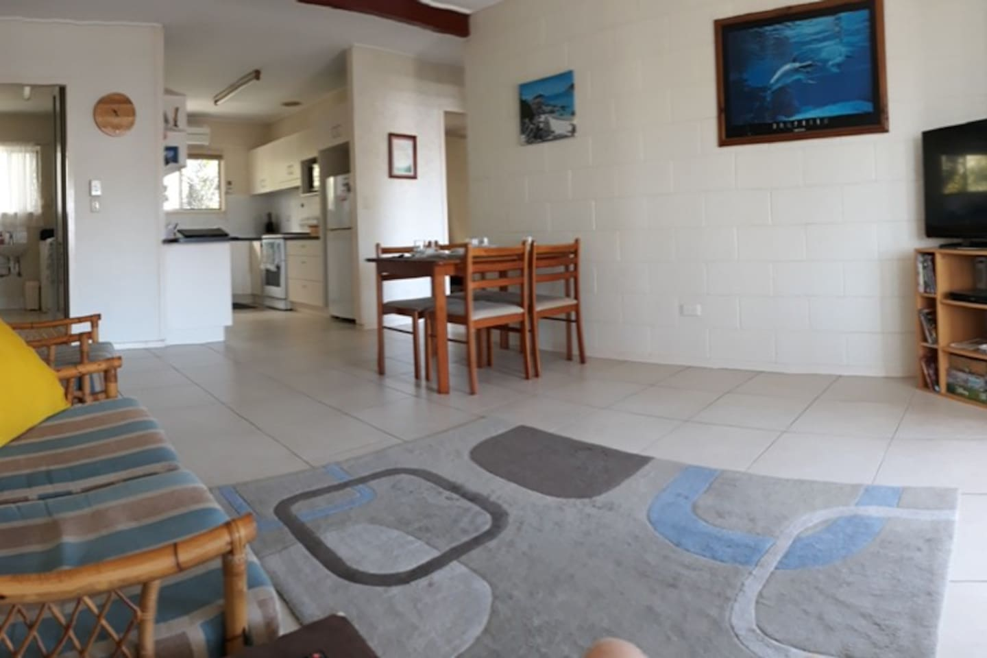 Panorama view of unit from the seating area looking towards the kitchen, laundry/shower room and the bedrooms with the sun-room behind