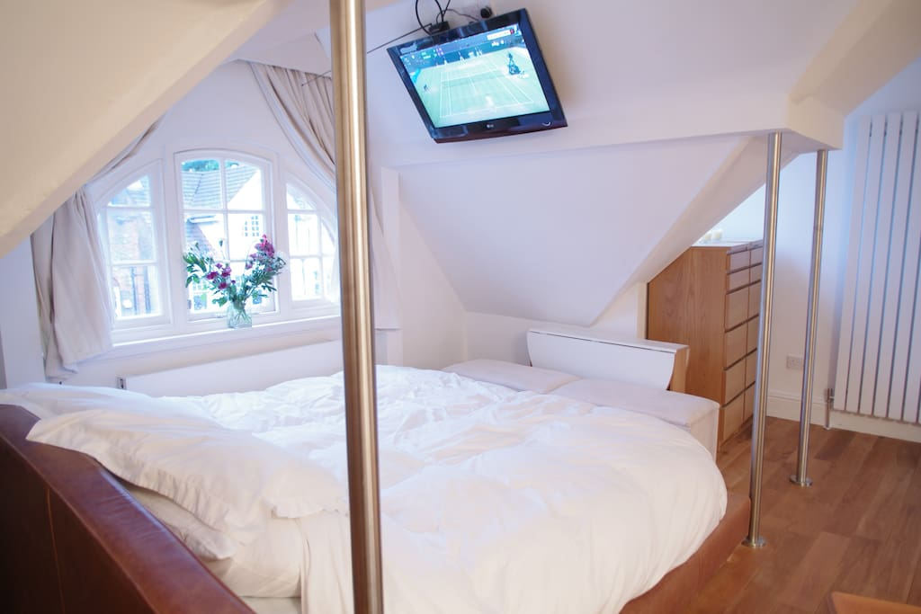 flat screen tv with freeview on the angled wall above the bed