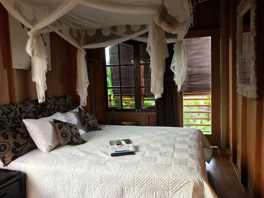Lumbung suite with wooden floors and walls, enclosed ensuite bathroom and romantic draped net. Has air-con and fan cooling, Queen bed, quality cotton linens and views from the veranda.