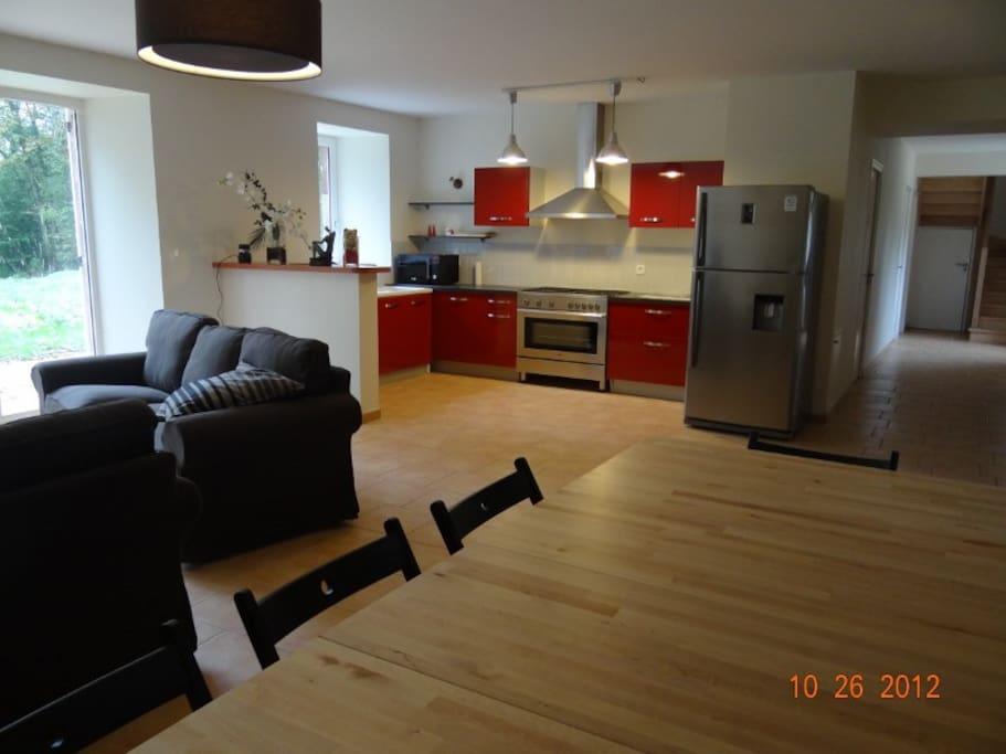 Une cuisine américaine et un grand living + TV.
