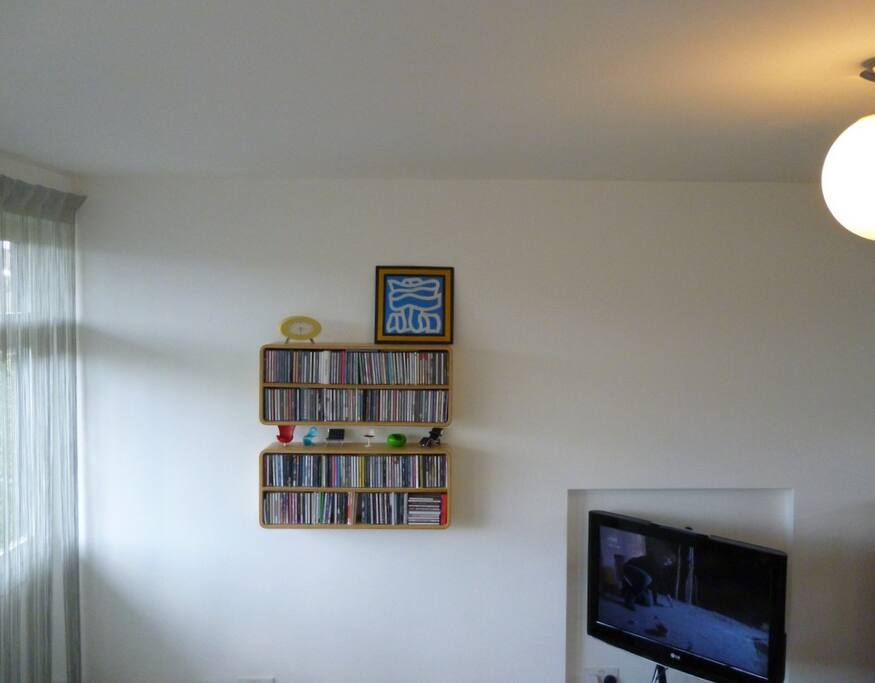 High level photo showing TV on wall bracket, CD rack and miniature chairs.