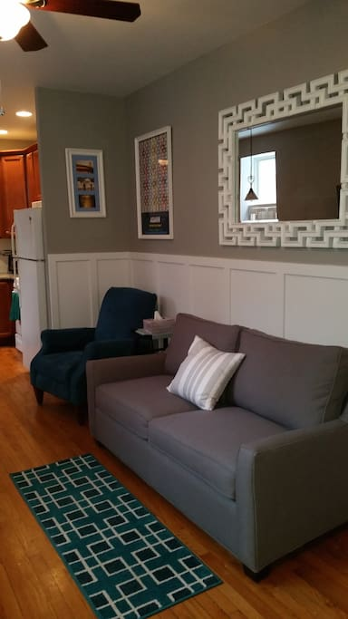 Living room with hardwood floors, new sofa and chair, and new ceiling fan (kitchen at the back)