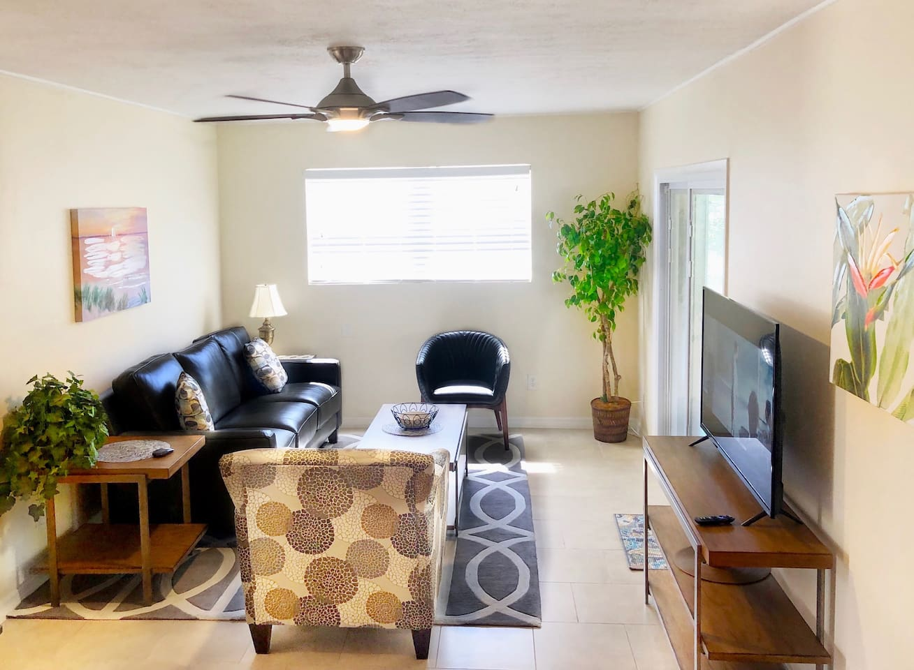 Living room with designer furniture and comfortable leather couch. High definition TV with RoKu TV service.
