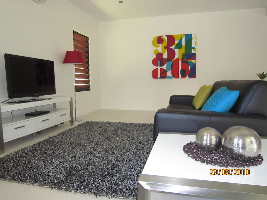 Your lounge area with a large TV comfortable sofa and air conditioning