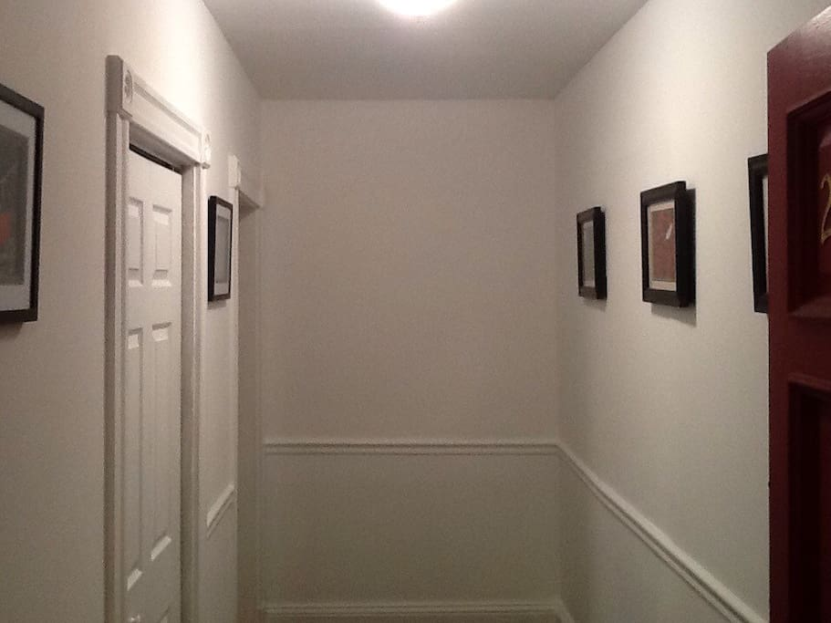 Entry way has bespoke photographic art on walls. Closet on left for coats and shoes.