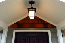 Ooow! Fancy cedar shingles and Craftsman light pump up the charm.