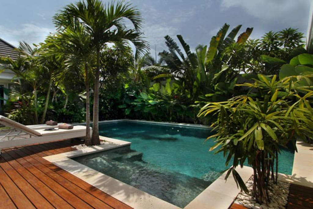 Pool view with its teak deck in a tropical garden.