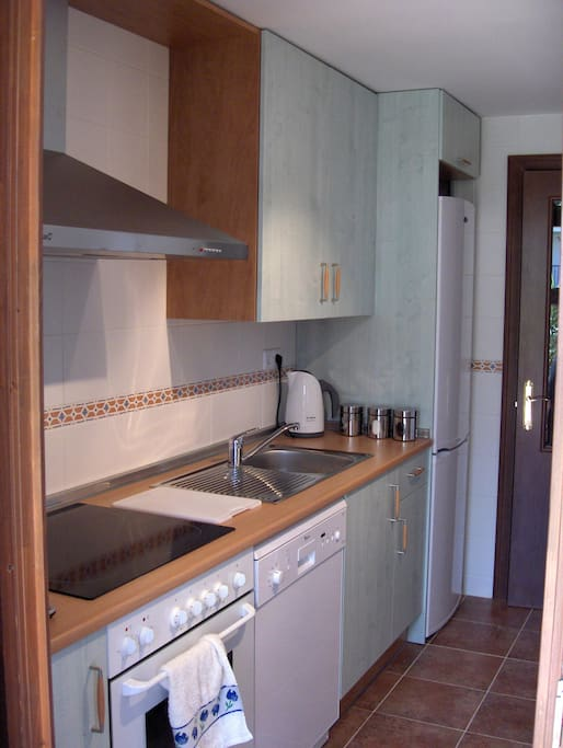 Fully loaded kitchen with fridge, freezer, dishwasher, microwave, toaster, kettle and coffee maker.