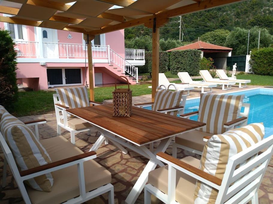 A wooden gazebo with two seater sofa and four chairs by the pool.