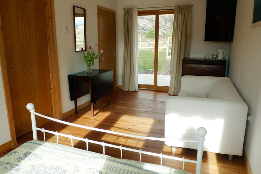 The bedroom with small seating area and doors on the decking area