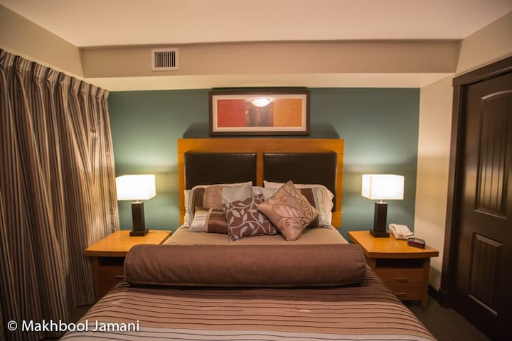 Room darkening drapes with a queen size bed and a memory foam mattress for a heavenly sleep!