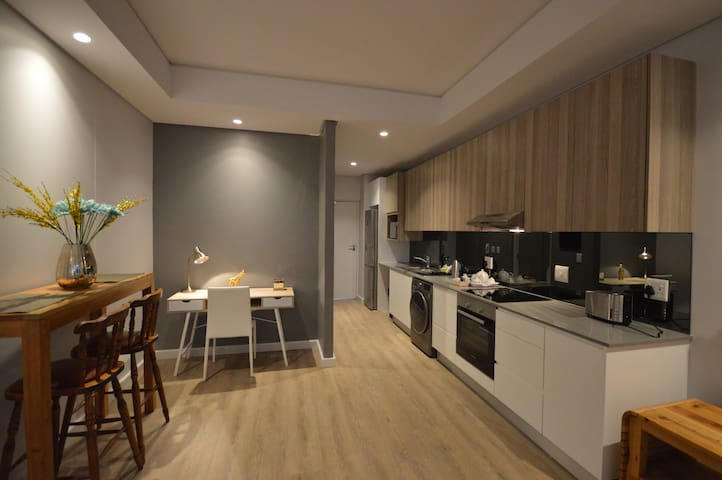 Work space, and the dining area, with the fully equipped kitchen, dish washer and washer/dryer included.