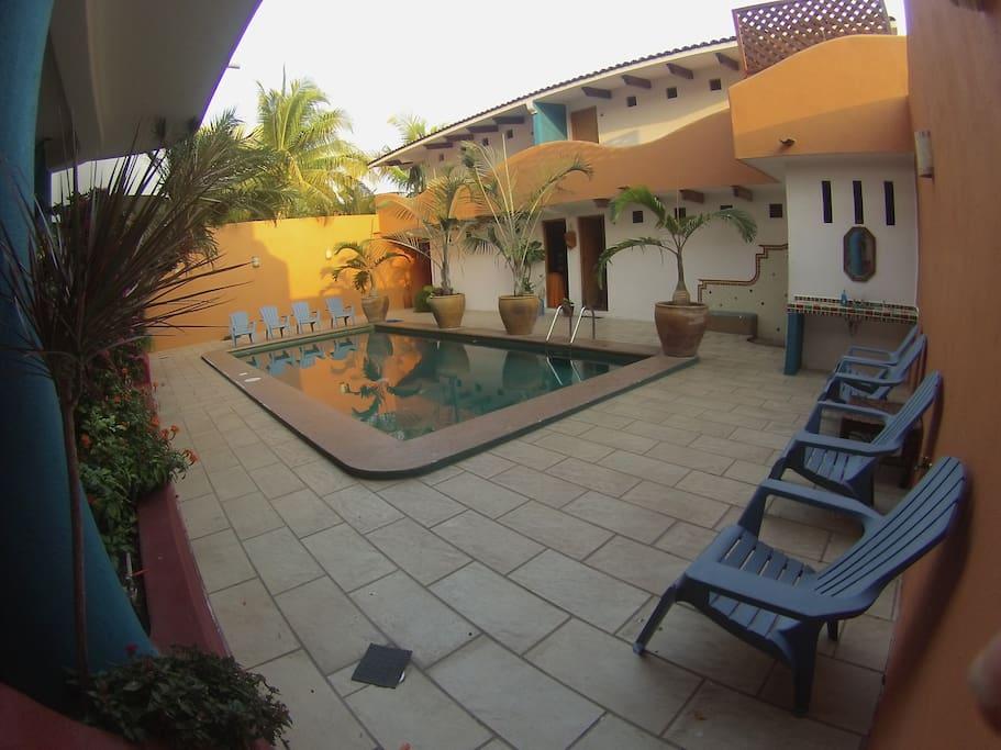 Area comun Alberca con sillas de sol y regadera.