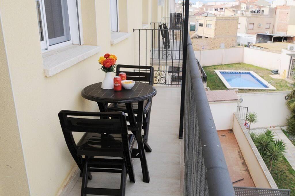 Una pequeña terraza con vistas a la piscina para desayunar o tomar el aperitivo al volver de la playa