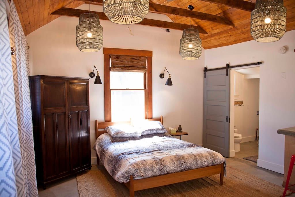 Brand new queen size Room and Board bed and vintage armoire. We used a reclaimed pocket door from a local turn of the century house as our sliding barn door on the bathroom.
