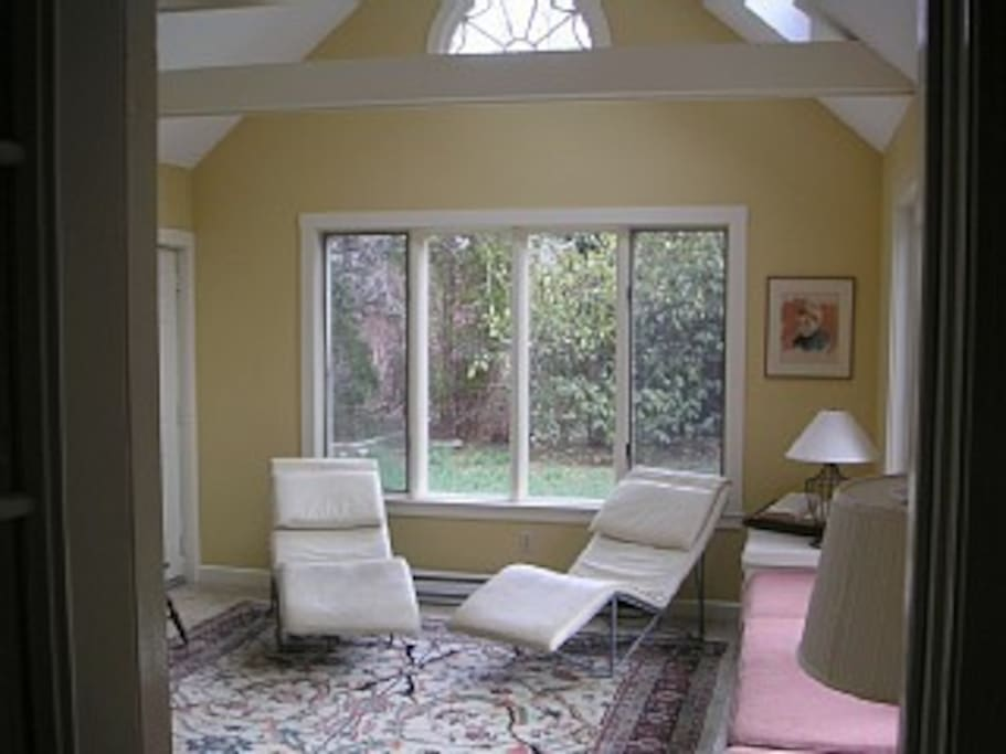 Sunroom with seating on a couch, cushioned bench, chairs and at a table