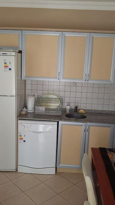 Kitchen has refrigerator, dishwasher and several kitchen wares