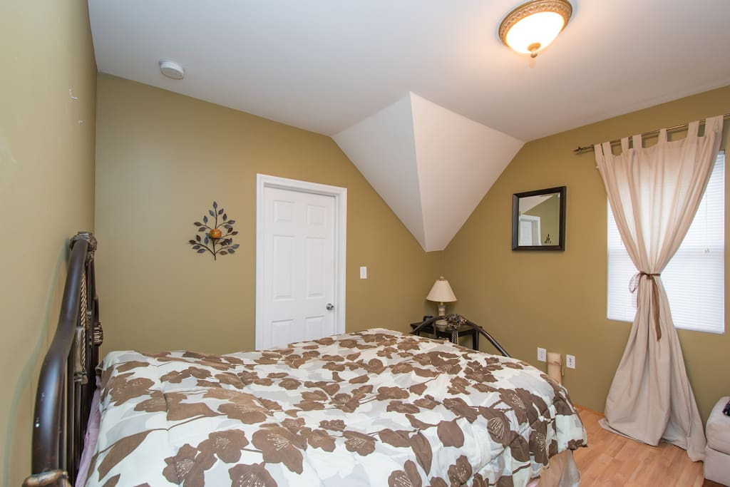 Bronze bedroom with walk-in closet. Cozy room with queen sized bed.