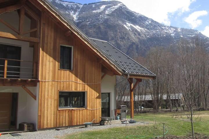 Maison (entière) au vert près des montagnes