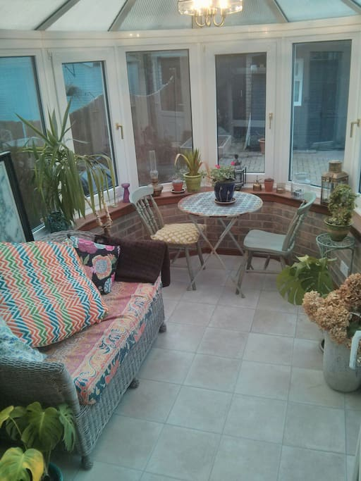 Sunny conservatory with small table full of plants!