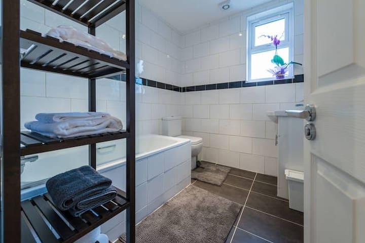 Modern bathroom across the hall. Towels provided.