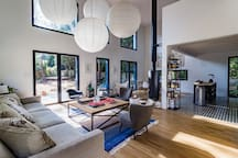 Open plan living with lounge, dining and kitchen areas overlooked by a mezzanine /  library