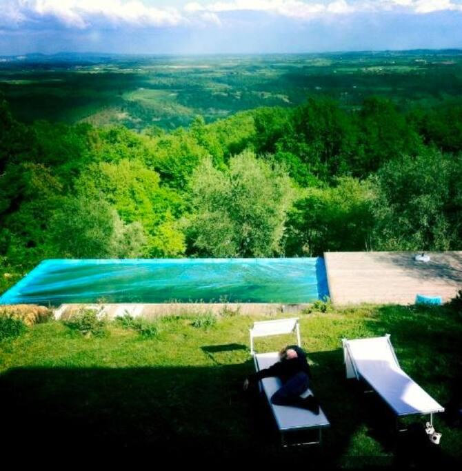 Il giardino della casa con la piscina visto dal terrazzo in legno del primo piano