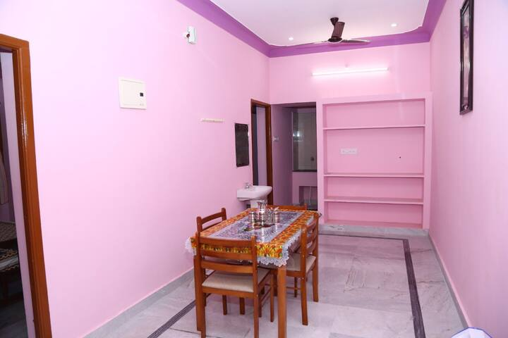 Living room consists of a fridge, dining table and 4 chairs, a washbasin and fan