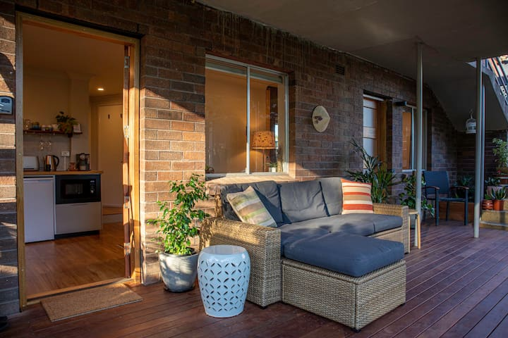 Private, self-contained apartment with covered deck and comfortable outdoor seating overlooking the beautiful garden