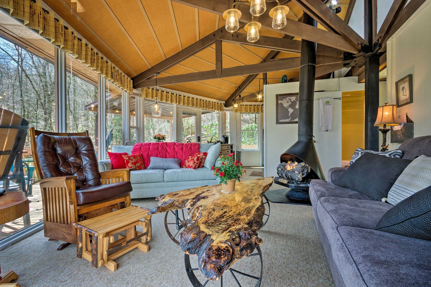 Living room view with vaulted ceilings, rustic decor, and natural wood furniture.