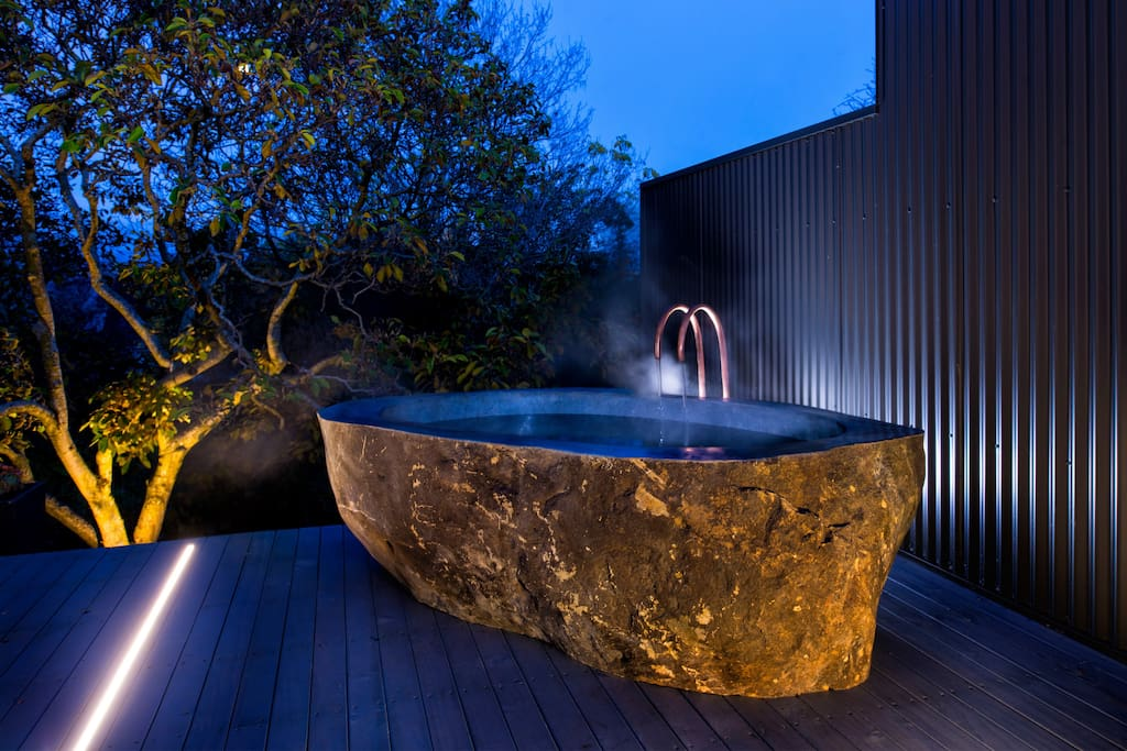 Private deck with outdoor bath carved from volcanic rock