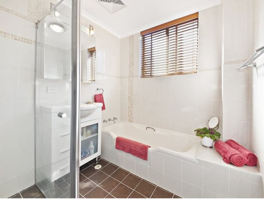 Clean and spacious bathroom with separate shower and bath. The shower fits two people